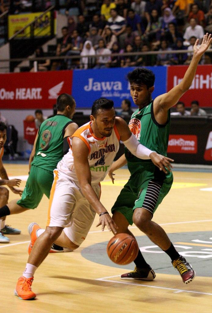 Center Pelita Jaya Energi Mega Persada Jakarta Adhi Pratama Prasetyo Putra (kiri) dihadang Muhammad Nur Aziz Wardana (Pacific Caesar) dalam laga di DBL Arena, Surabaya, Rabu (21/1).