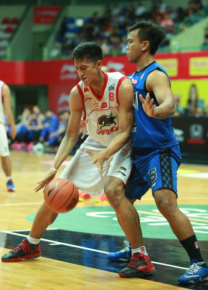 Center Garuda Kukar Bandung Muhammad Dhiya Ul'haq (kiri) dijaga Evin Istianto Hadi (Stadium Jakarta) dalam laga di GOR UNY, Jogjakarta, Minggu (15/3).