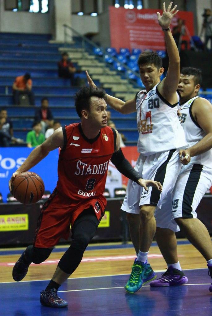 Small forward Stadium Jakarta Wijaya Saputra (kiri) melewati hadangan Mei Joni (Hangtuah Sumsel IM) dalam lanjutan IndiHome NBL Indonesia 2014-2015 di C-Tra Arena, Bandung, Kamis (26/3).