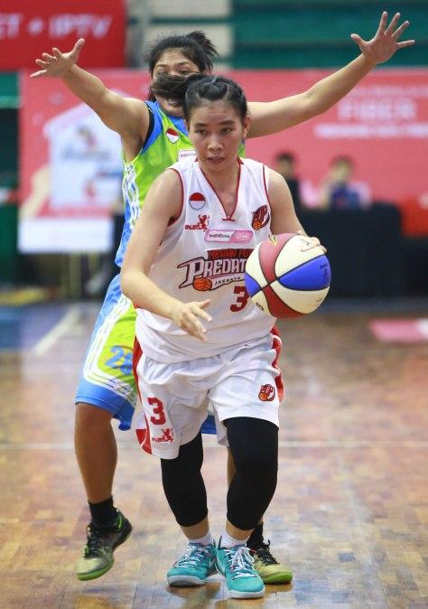 Power forward Merah Putih Predators Jakarta Yosiana Rosemary melewati penjagaan Marjorice Fedora Tsarine dari Sritex Dragons Solo dalam laga di C-Tra Arena, Bandung, Kamis (26/3).