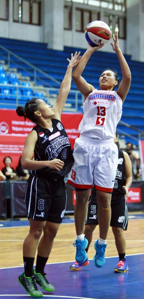 Power forwad Sahabat Wisma Sehati Semarang Yuni Anggraeni melepaskan tembakan dijaga oleh Fitryana Sari Dewi (Merah Putih Predators) dalam laga di C-Tra arena, Bandung (29/03)