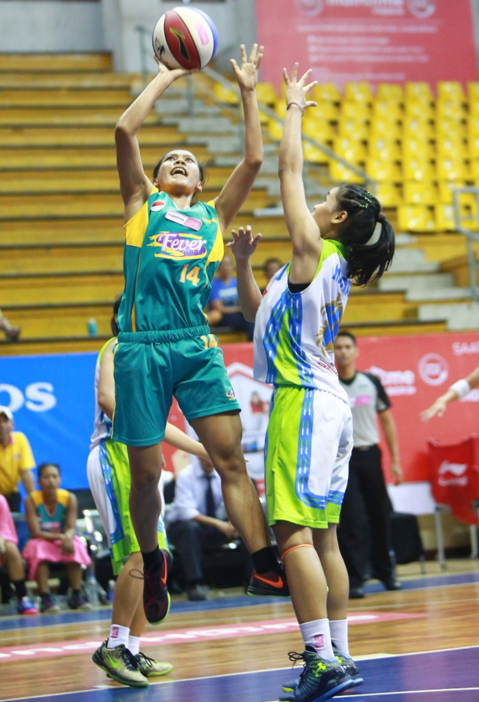 Power forward Surabaya Fever Mega Nanda Perdana Putri (kiri) melepaskan tembakan dijaga Lophy Mora Christya (Sritex Dragons Solo) di C-Tra Arena, Bandung, Sabtu (28/03).