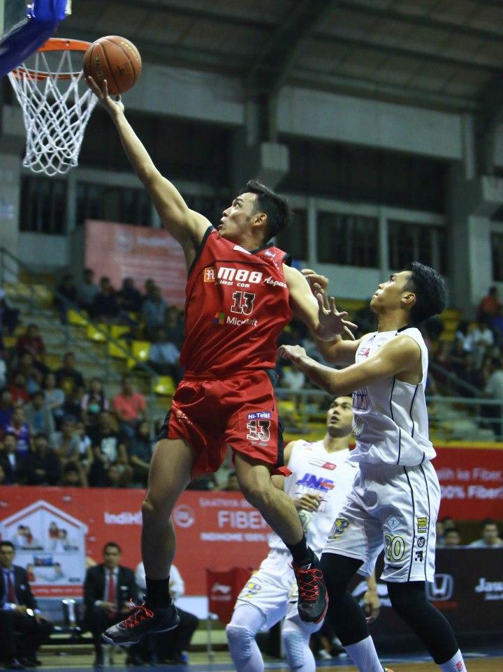 SAPU BERSIH: Shooting guard M88 Aspac Jakarta Ebrahim Enguio Lopez (kiri) melakukan lay up melewati hadangan Teddy Apriyana Romadonsyah (JNE BSC Bandung Utama) dalam laga di C-Tra Arena, Bandung, Minggu (29/3).