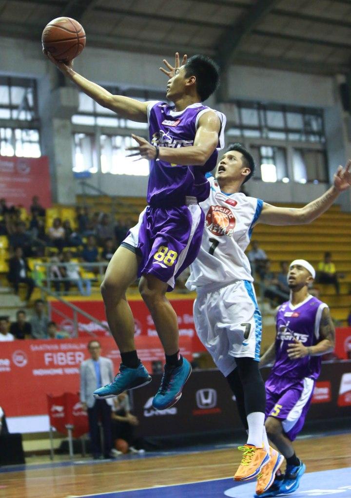 Shooting guard CLS Knights A.A. Ngurah Wisnu Budidharma S. (kiri) melakukan lay up melewati penjagaan Handoyo Cahyo Saputro (Pacific Caesar Surabaya) dalam laga di C-Tra Arena, Bandung, Minggu (29/3).