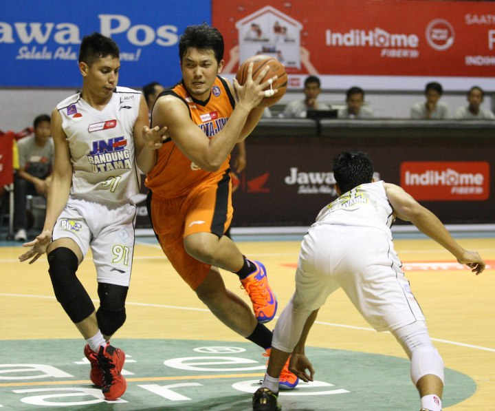 Power forward Pelita Jaya Energi Mega Persada Ponsianus Nyoman Indrawan (tengah) berusaha melewati penjagaan Azhari Rahmat (kiri) dan Surliyadin dari JNE BSC Bandung Utama dalam laga di DBL Arena, Surabaya, Kamis (9/4).