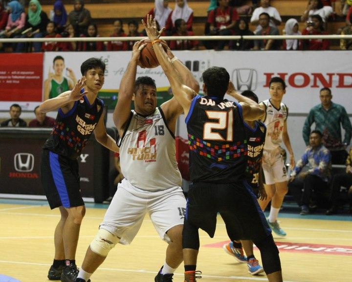 Center Hangtuah Sumsel IM Toni Sugiharto (tengah) berusaha melewati penjagaan Raylly Pratama (kiri) dan Boy Elimar Damanik dari NSH GMC GSBC Jakarta dalam laga di DBL Arena, Surabaya, Jumat (10/4).