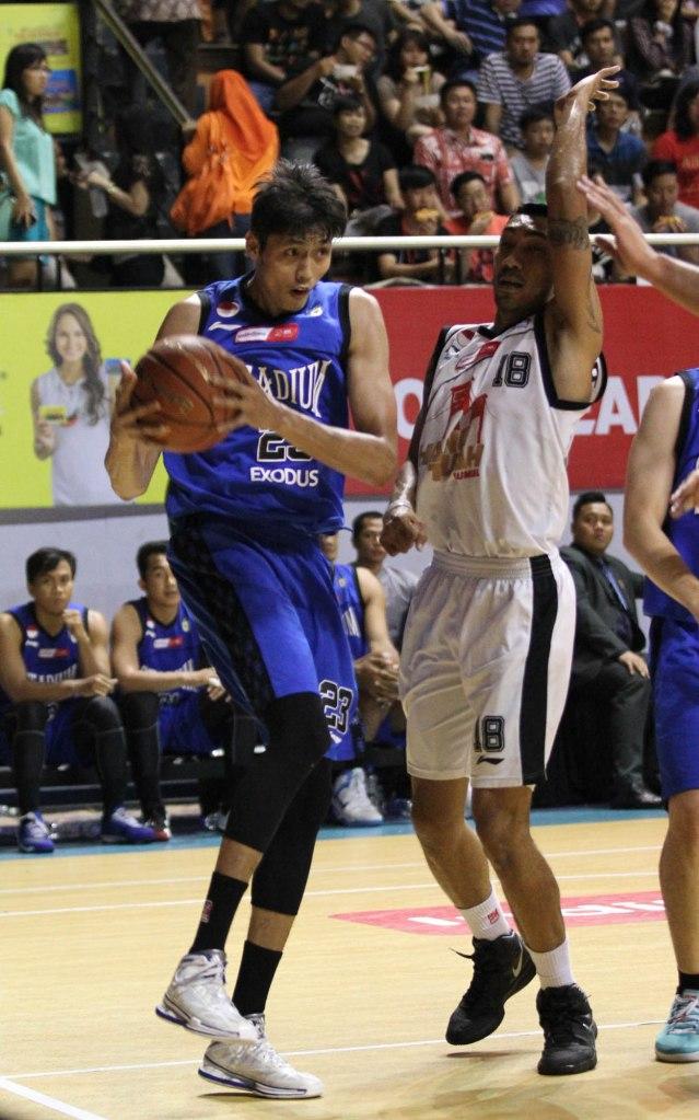 Center Stadium Jakarta Ruslan (kiri) berusaha menembus pertahanan Yan Stiven Pattikawa dari Hangtuah Sumsel IM dalam laga di DBL Arena, Surabaya, Minggu (12/4).