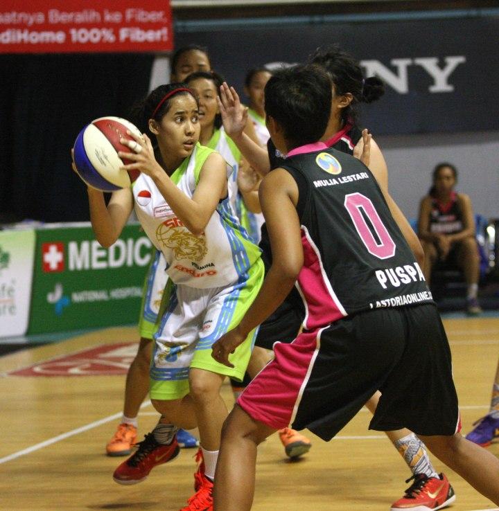 Small forward Sritex Dragons Solo Tania Rasidi (kiri) dihadang Puspa Lalita Anggayasti dari Rajawali Bandung dalam laga di DBL Arena, Surabaya, Kamis (9/4).