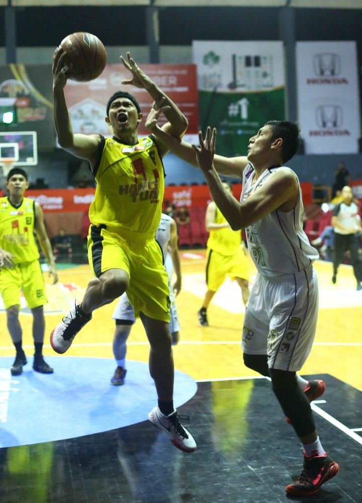 Shooting guard Hangtuah Sumsel IM Andre Ekayana (kiri) melakukan lay up melewati penjagaan Azhari Rahmat  dari JNE BSC Bandung Utama dalam laga di Hall Basket Senayan, Jakarta, Minggu (3/5).